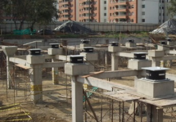 Photo of several seismic isolators at large construction site.