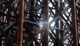nstruction worker welding a large iron scaffolding.