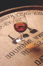 Glass of bourbon sitting on top of a barrel filled with bourbon whiskey  Photo caption credit: Distilled Spirits Council of the United States, Inc.